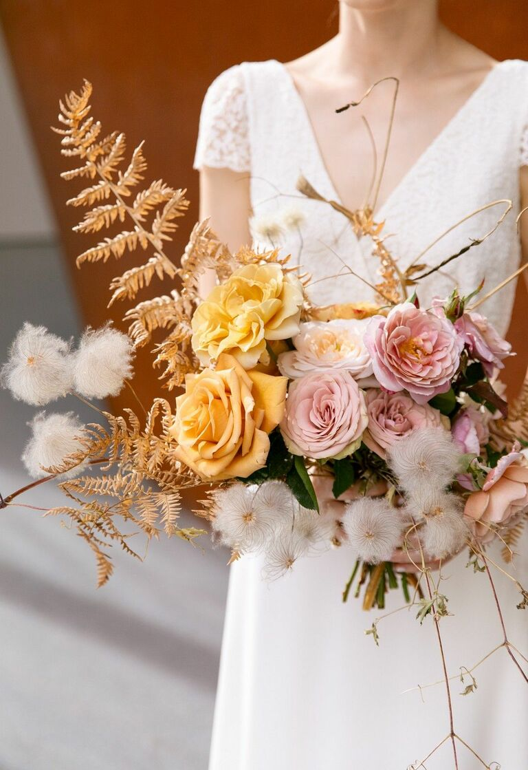 Bride holding fern and rose bouquet