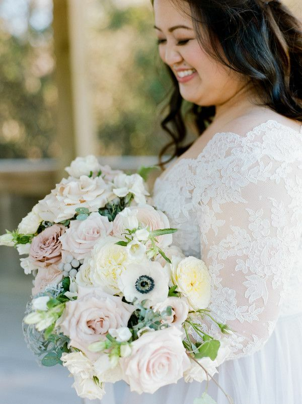 Bride holding bouquet with white, pink and gray flowers