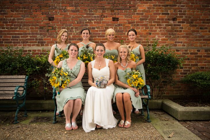 Kasi's bridesmaids wore mixed pale green J.Crew dresses with DIY sunflower bouquets.