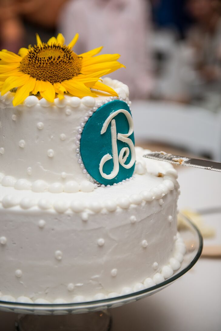 """A fresh sunflower topped the simple two-tiered buttercream cake with swiss dots and pearl piping. """"A retired family friend graciously made our cake because she knows, no one can make cake like hers!"""" says Kasi."""