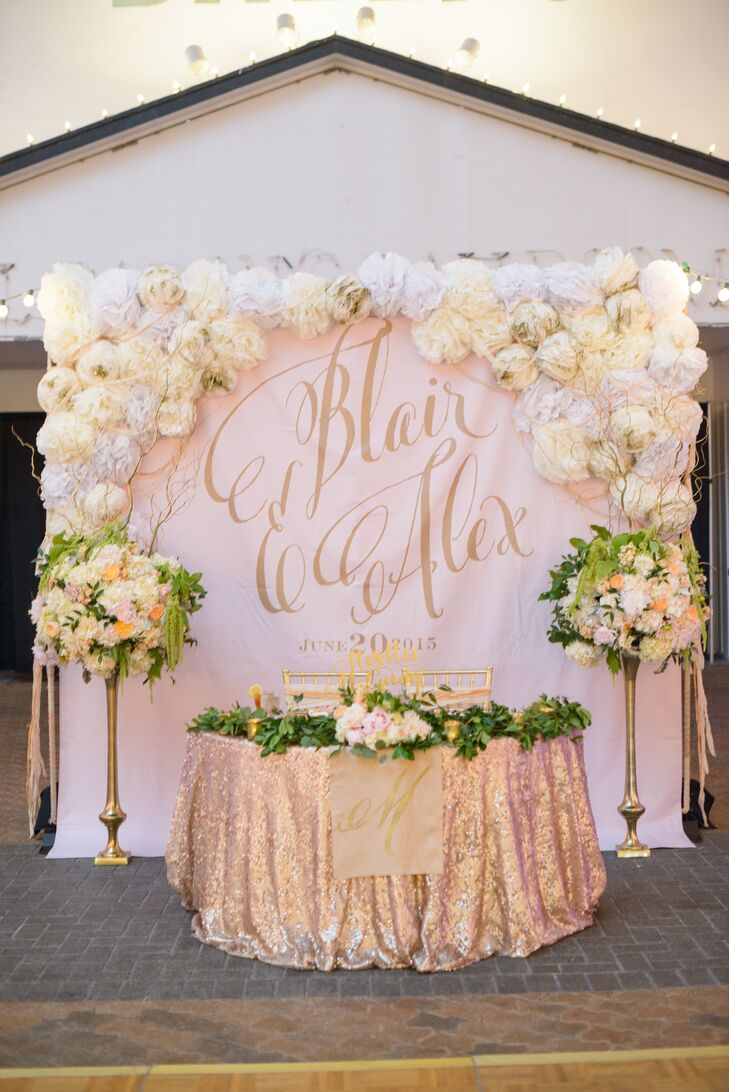 """Blair and Alex's sweetheart table display was nothing short of wow-worthy! It had a bold blush backdrop with their names in gold calligraphy, which matched their metallic gold table linens. White and ivory paper flowers decorated the backdrop, while a pair of lush arrangements including hydrangeas, garden roses and amaranthus in tall gold vessels stood on either side. A leafy garland decorated the top of their dining table along with a gold """"Mr. & Mrs. McCurdy"""" to match the gold votives and a gold """"M"""" hanging in front. They spared no detail here!"""