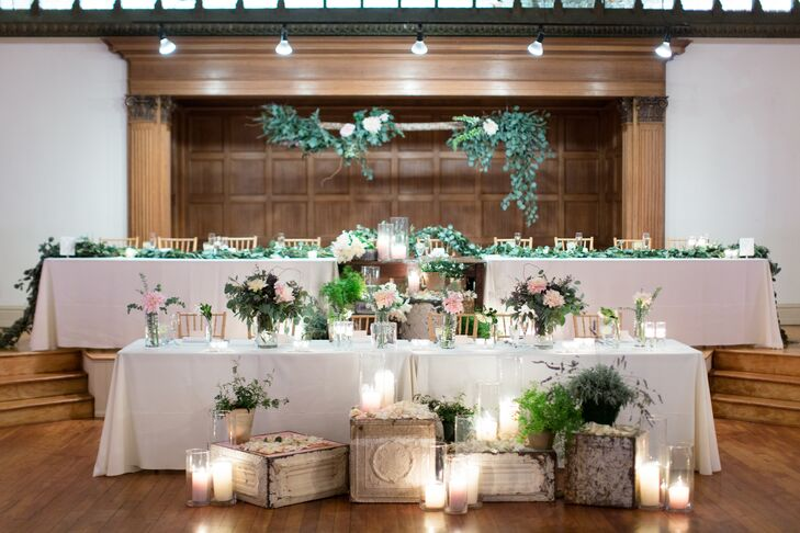 At the reception, the head table was covered with crisp white linen, draped with eucalyptus garlands and set with glowing white votives. To continue the rustic, romantic feeling through the reception, vintage white boxes were placed throughout and topped with similar candles and greenery.