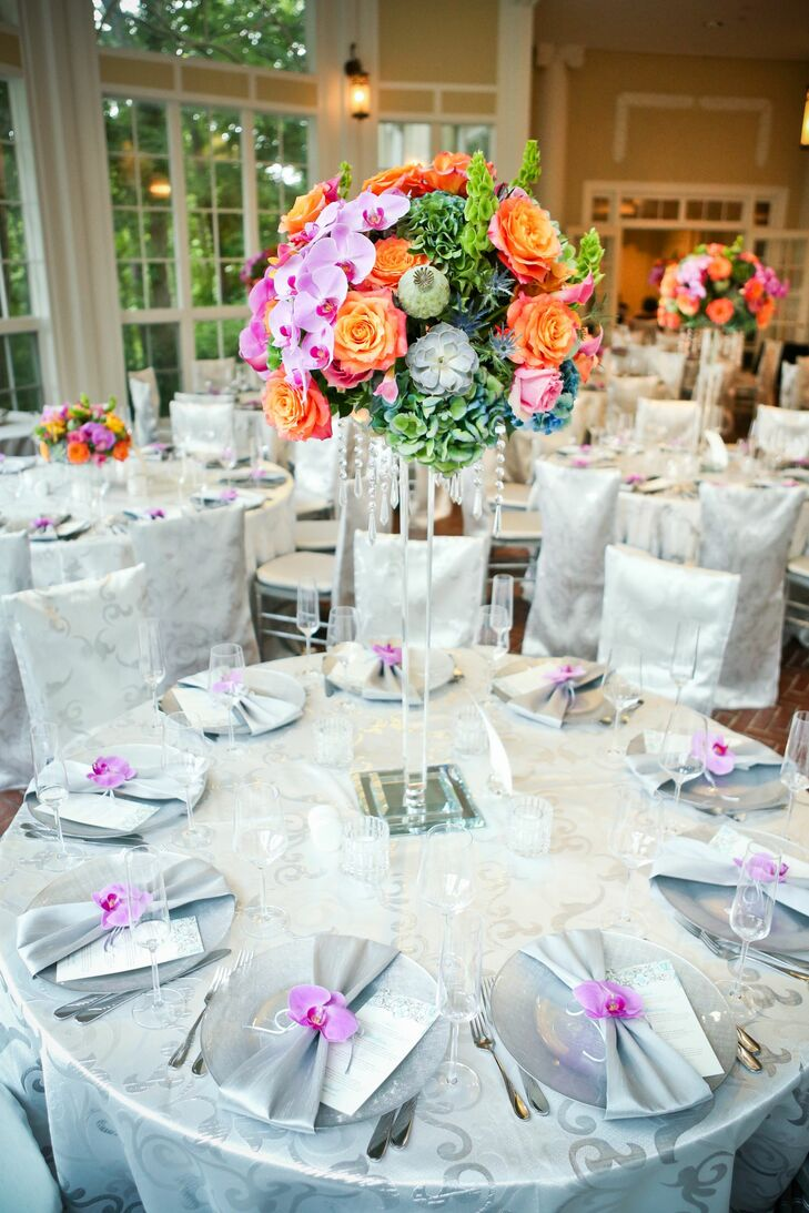 """""""We wanted to have a lush romantic feel for the flowers, as if we were standing in a slightly overgrown, ripe garden,"""" says Sharon. The tall centerpieces included phalaenopsis orchids, orange roses, blue thistle, poppy pods, succulents and more."""