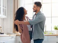 Couple in a committed relationship dancing in the kitchen.
