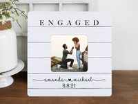 White wooden style background with 'Engaged' in simple serif above photo and names below
