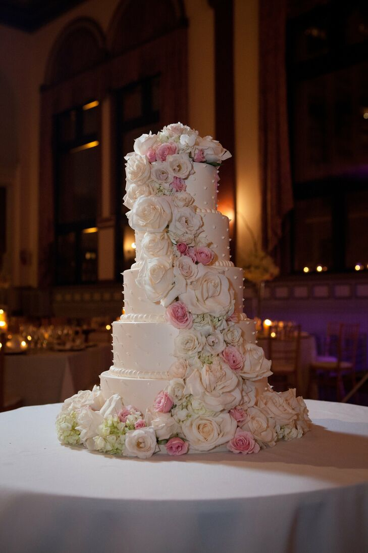 The five-tiered cake was adorned with delicate ivory dots and topped off with an array of fresh Vendela roses, blush spray roses and ivory hydrangeas cascading down the tiers.