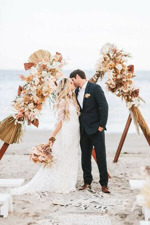 The Bride and Groom Share a Kiss in Front of the Wedding Arch