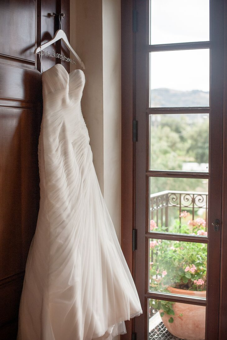 Christine wanted a classic dress, and when she came across the Pronovias Orel gown during her travels in Spain, she knew she had found her inspiration. Little did Christine know she would find the dress in a bridal store that carried an exact replica. The ivory strapless gown with a sweetheart neckline had tulle wrapped around the silhouette, bunching to one side.