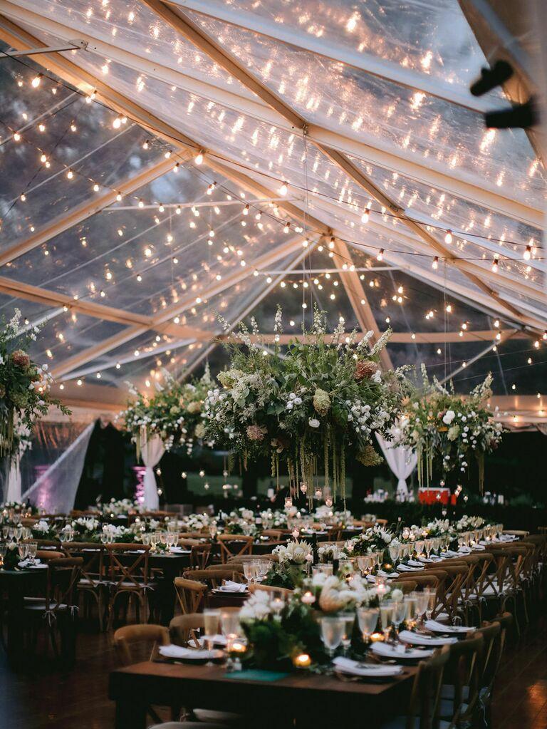 String lights strung under tended outdoor wedding reception