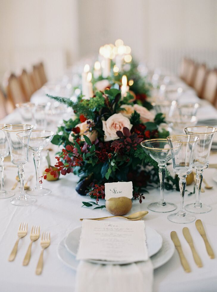 The tablescape captured the sophisticated setting and drama of a still life painting, with crisp white linens dressed to the nines with gold cutlery, brass candlesticks, fresh fruit and romantic arrangements of blush roses, wispy greenery and moody burgundy and plum-colored blooms.