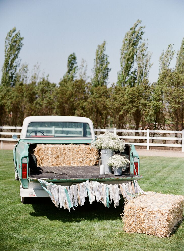During cocktail hour, the appetizers and snacks were displayed on the tailgate of a vintage white and turquoise truck decorated with a string of colorful tassels.