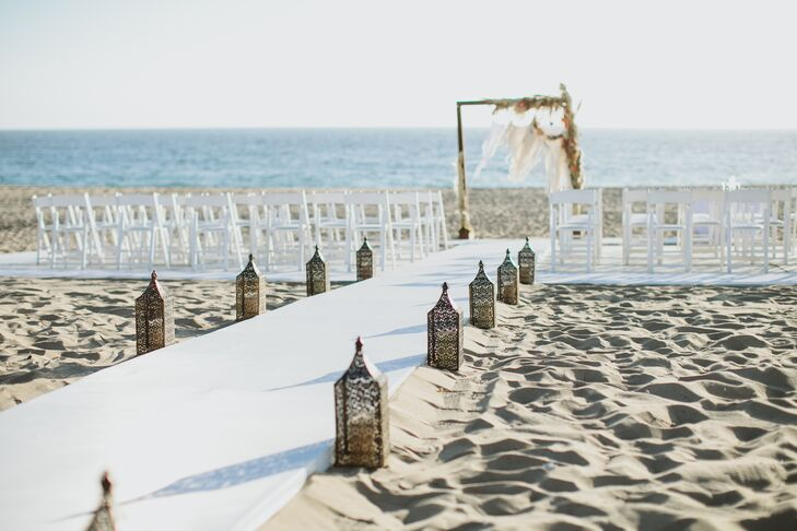"""A sturdy white platform aisle lined with lanterns led to the dream catcher wedding arch where Gwynne and David exchanged vows. """"I wanted a boho beach wedding with rich orange sunset colors in the flowers,"""" Gwynne says. """"The Sunset Restaurant was the perfect location because we were able to have our ceremony right on the beach at sunset."""""""