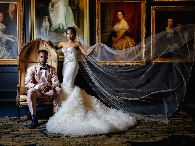 Bride and groom posing in front of vintage art photos