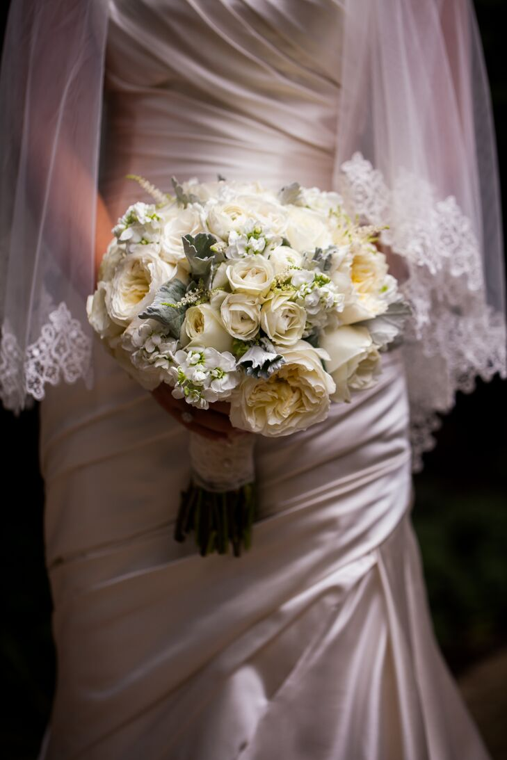 The bridal bouquet was a lush, all-white, hand-tied bouquet made of roses, garden roses, stock, spray roses, ranunculus and astilbe with touches of dusty miller.