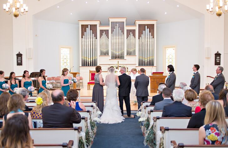 """The First United Methodist Church of Chatham in Chatham, Massachusetts, was a must for Lindsey and Keith's ceremony. """"After attending a service, meeting the congregation and speaking with the pastor we felt very at home,"""" Lindsey says. """"The beautiful clock tower, stained glass windows and wooden pews were the exact Cape touch we wanted for our ceremony."""""""