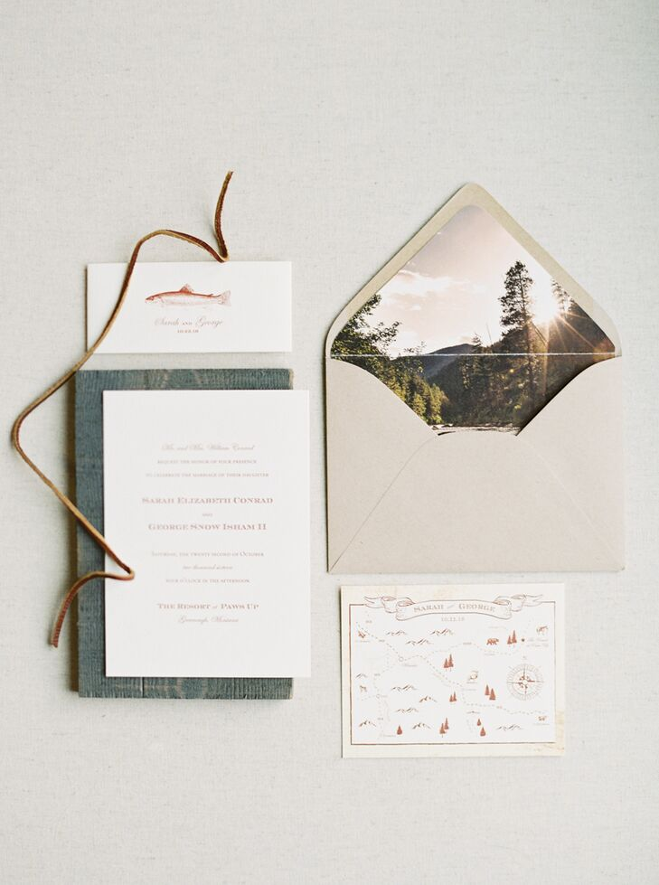 """Noteworthy designed rustic, vintage-inspired invites for Sarah and George. """"The invitations had a vintage-looking map of northwest Montana with a print of a brown trout on the band,"""" Sarah says. """"A photo of Rock Creek, a river outside Missoula, was printed inside the envelope."""""""