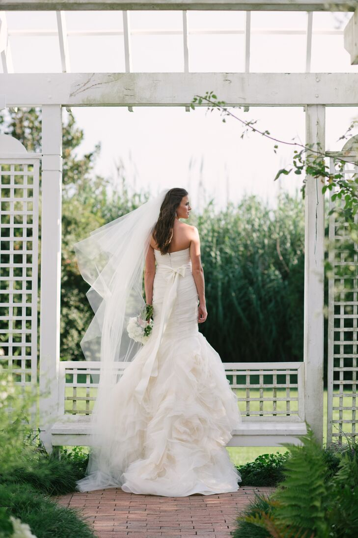"""""""My dress was very soft and whimsical, almost ethereal, with lots of tulle and a beautiful organic layering at the bottom,"""" says Casey. """"The long train was my favorite part of my wedding day ensemble— it looked so beautiful from behind!"""""""