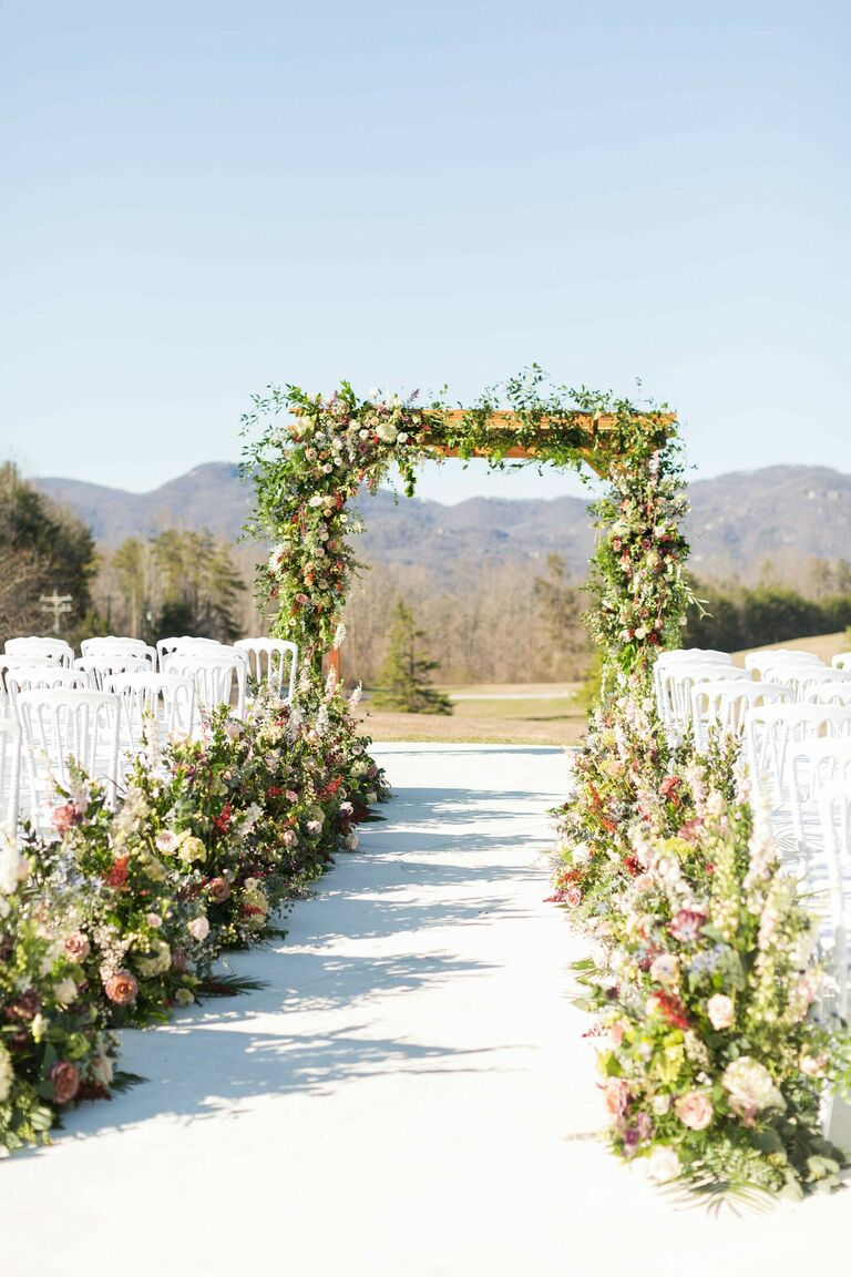 Outdoor wedding ceremony with greenery-lined aisle and mountain views