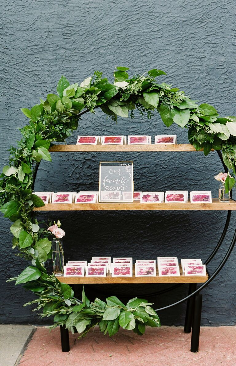 Escort card display with circular shelving unit covered in greenery