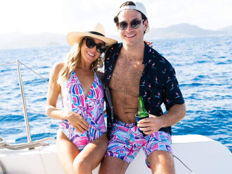 Couple wearing matching colorful tropical print bathing suit and swim trunks
