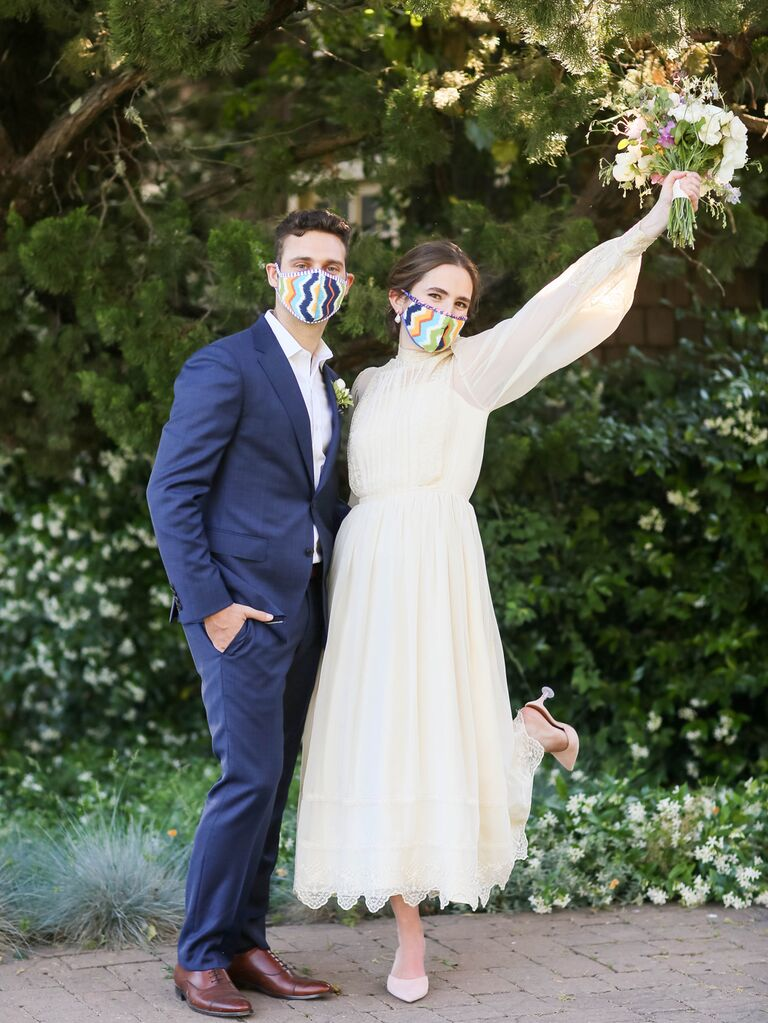 Bride and groom wearing matching colorful wedding masks