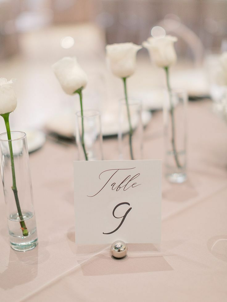 Minimal rose centerpieces and simple black-and-white table number