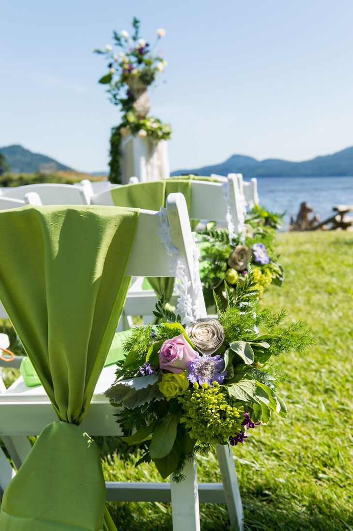 Arrangements of rose, fern, paper flowers and lavender hung from the aisle seats at the outdoor ceremony.