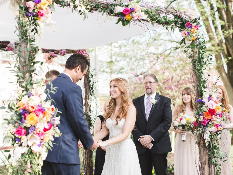 Bride and groom stand below a ceremonial chuppah