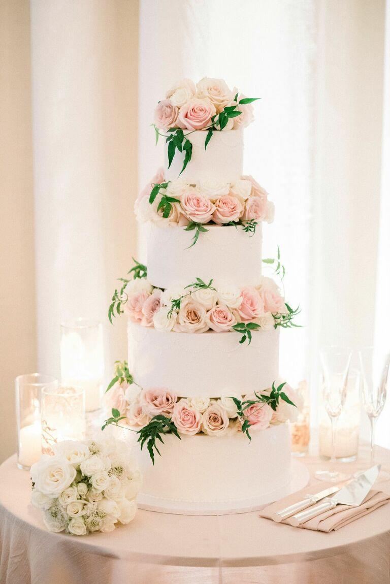 White four-tier cake with pink roses between each tier