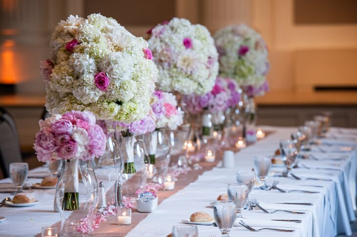 The altar decorations and bridesmaid bouquets were repurposed at the reception as head table decor. The tall arrangements of hydrangeas and roses fit in perfectly with the pink and white color scheme.