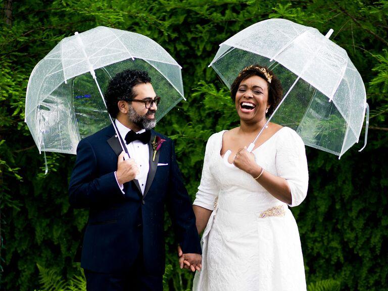 Bride and groom holding umbrellas on rainy wedding day