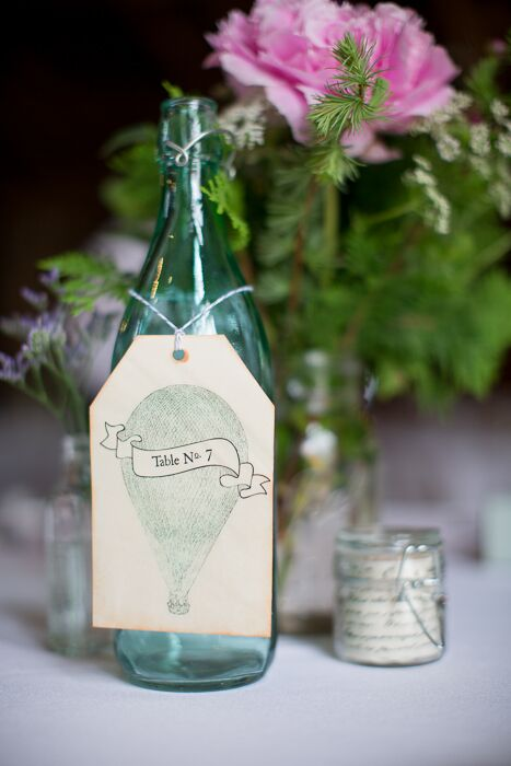 Gift tags with illustrations of hot air balloons hung from glass bottles for the vintage inspired table numbers.