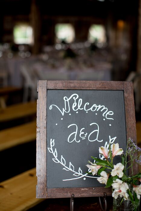 A chalkboard sign welcome guests into the reception barn.