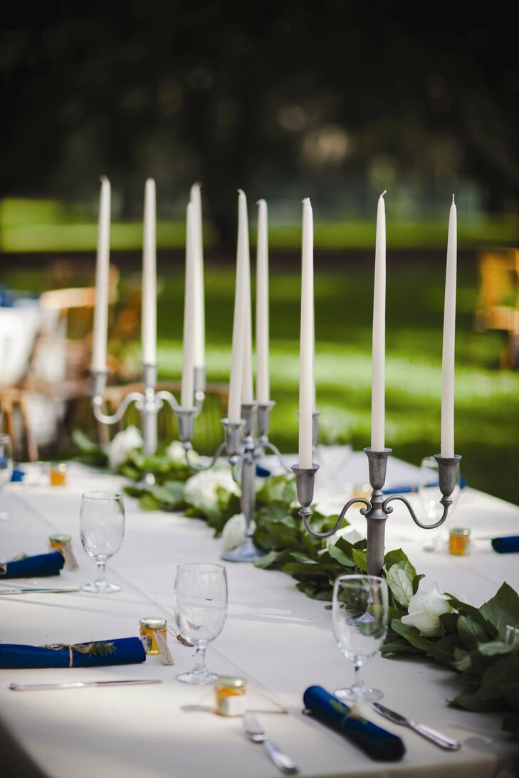 Salal leaf runners were studded with white roses and topped with rustic pewter candelabras.