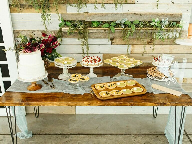 Rustic wood farmhouse dessert table with wedding cake, cupcakes and mini pies