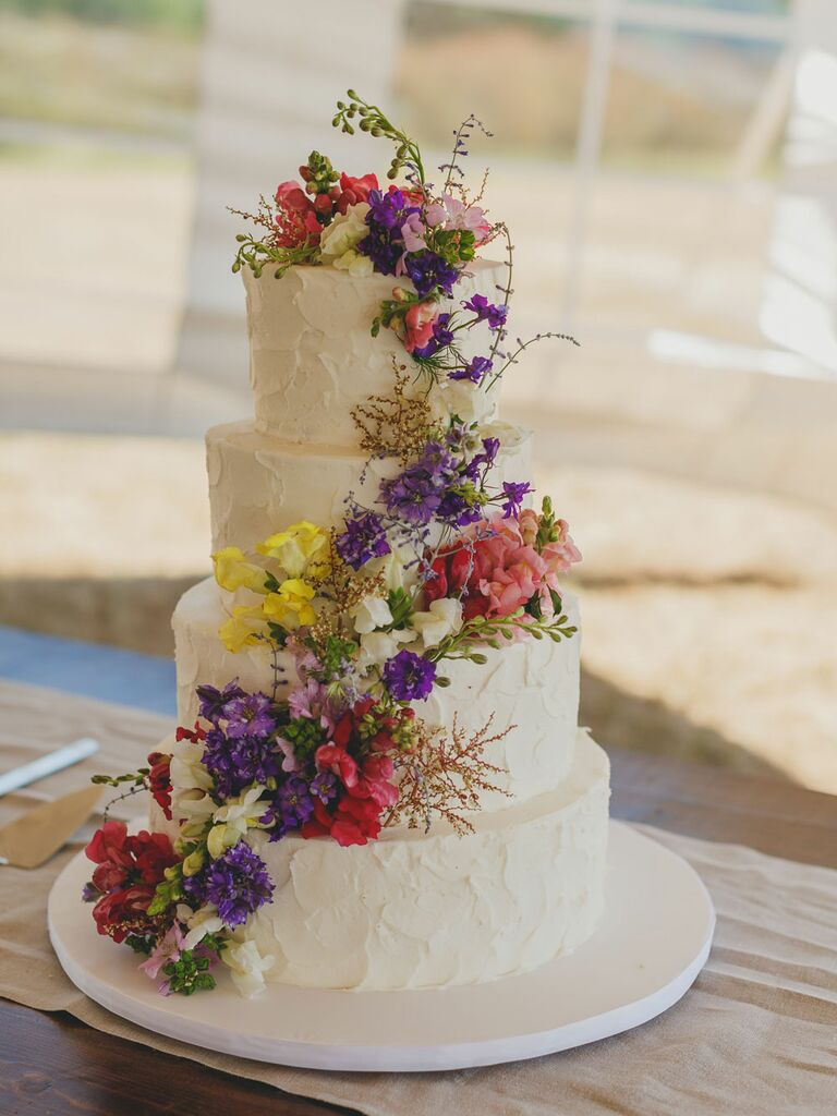 Four-tier white rustic wedding cake with cascading wildflowers