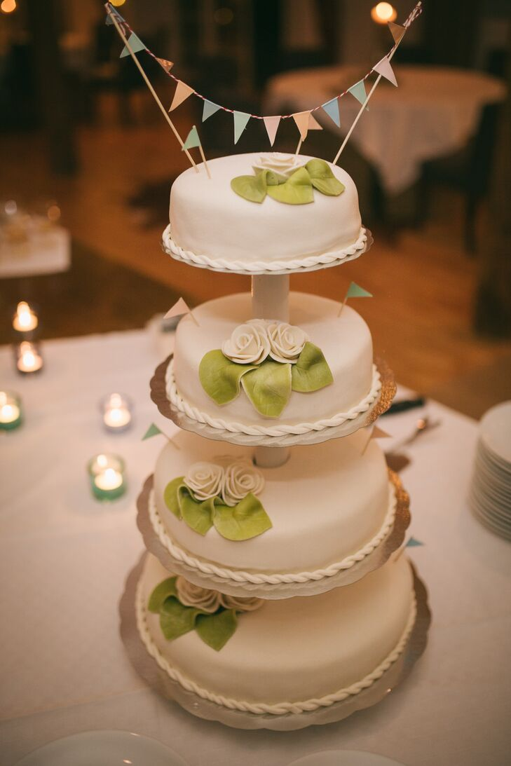 Ulrika and Victor enjoyed a four-tiered wedding cake with each tier on a separate, stacked stand. Each layer was decorated with white fondant roses and green fondant leaves. It was topped with a strand of mini bunting.