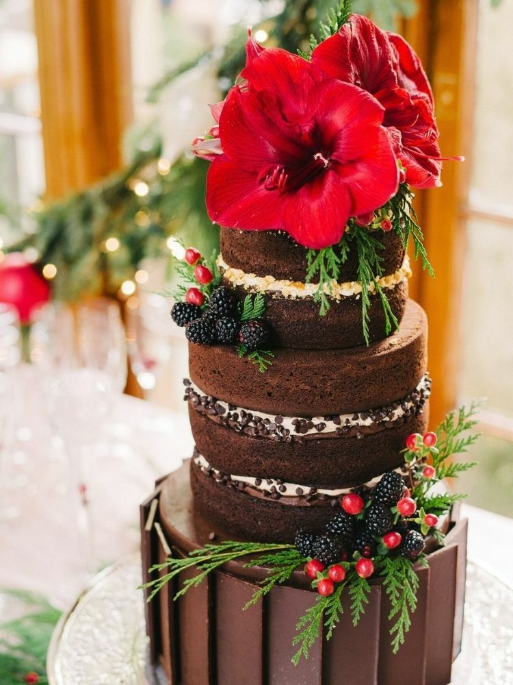 Chocolate wedding cake topped with red amaryllis bloom