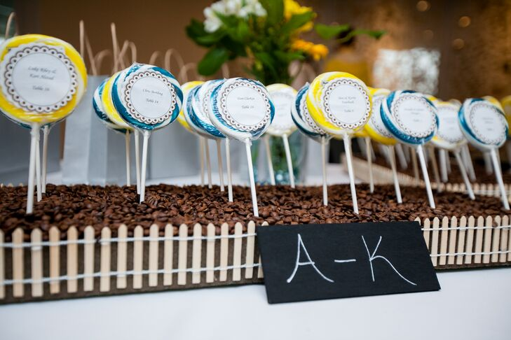 As escort cards, Dawn and Chad labeled blue and yellow lollipops with their guests' names and table numbers. These lollipops were arranged to look like flowers in a garden.