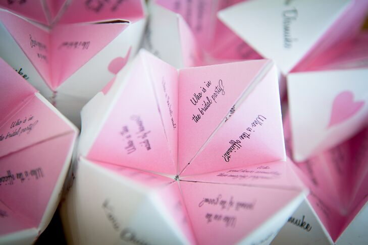 """The bride and groom made custom pink and white """"cootie catchers"""" for their ceremony program, full of facts about the groomsmen and bridesmaid. They wanted their guests to become better acquainted with their wedding party during their ceremony."""