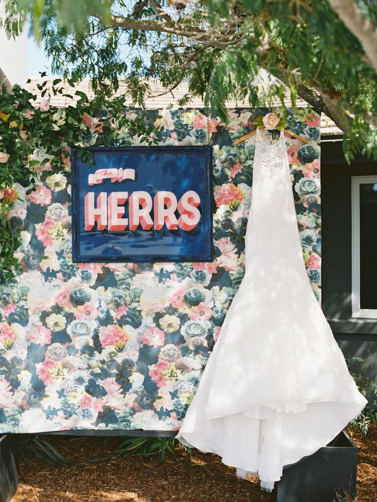 Retro pink custom wedding signage hanging on floral wallpaper next to wedding dress