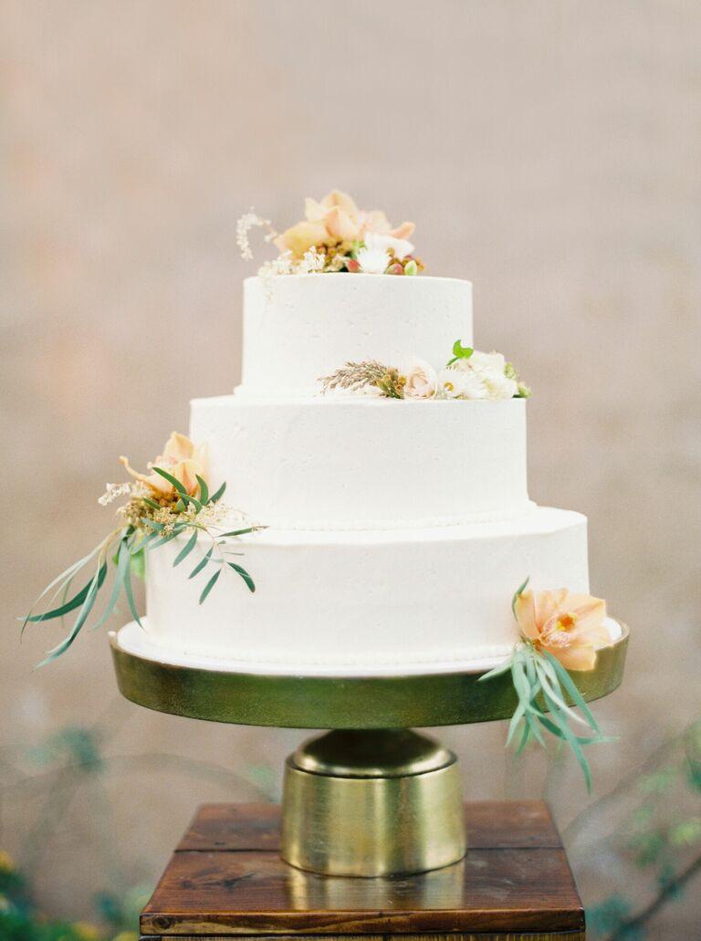 Minimal white three-tier wedding cake on gold cake stand