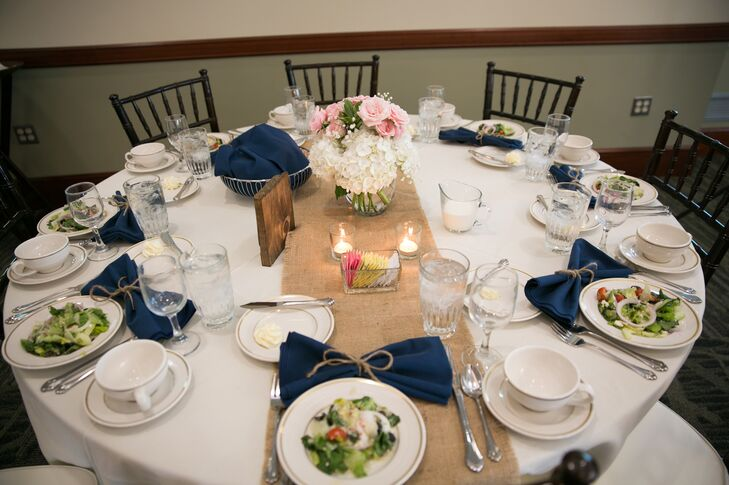 """""""The table linens were ivory with burlap table runners. Each table had a floral centerpiece along with votive candles, floating candle with branches in the vase and wooden table numbers,"""" says the couple."""